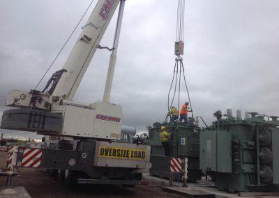 Crane helping secure large load